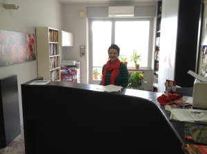 School secretary Giulia waves from behind the Comitato Linguistico desk.